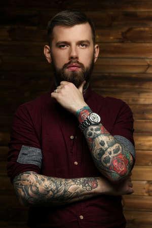 tattoed: Masculina Tattoed presenta sobre la pared de madera