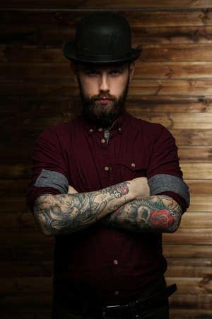 tattoed: Tattoed male posing over wood wall Stock Photo