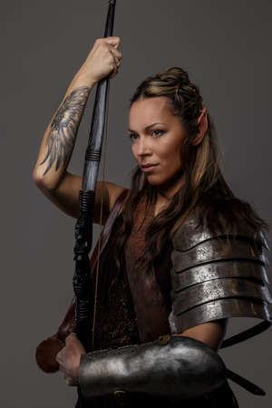 Elf woman in armor holding sword. Isolated on grey Archivio Fotografico