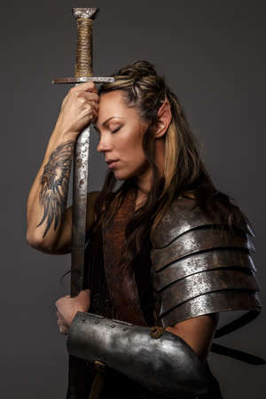 the iron lady: Elf woman in armor holding sword. Isolated on grey Stock Photo