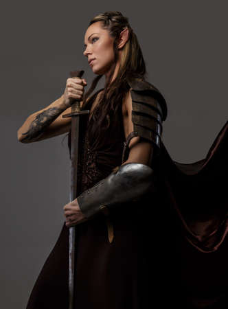 Elf woman in armor holding sword. Isolated on grey Stock Photo
