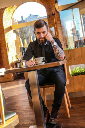 tattoed: Tattoed man sitting in a cafe