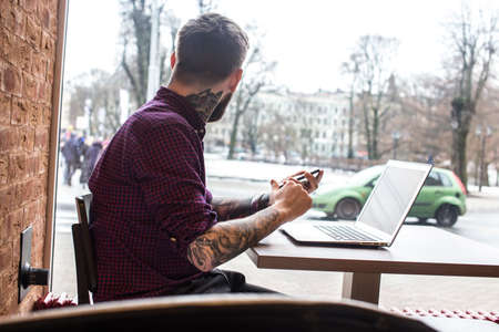 Male with tatoos and beard sitting at the table and working with laptop.