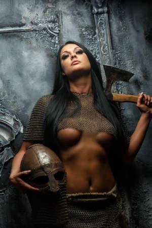 cavaliere medievale: Impressionante giovane donna in antiche armature con ascia e casco su sfondo grigio.