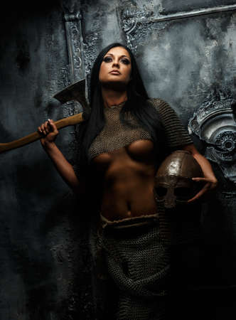 fighters: Awesome young woman in ancient armor with axe and helmet on grey background. Stock Photo