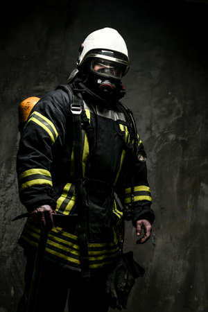 Firefighter in oxygen mask and axe on grey background. photo