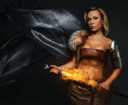 Middle age woman with sword in fire on grey background