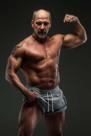 Strong muscular middle age man posing in studio. Isolated on grey.