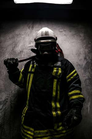 firefighter: Bombero en m�scara de ox�geno y el hacha sobre fondo gris. Foto de archivo
