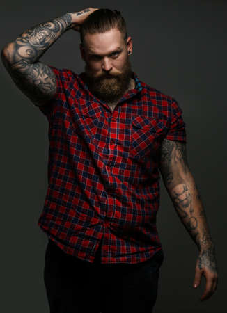Man with tattoo on arms posing in studio. Isolated on grey. Foto de archivo