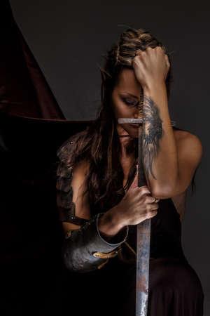 maquillaje fantasia: Mujer Elf en celebración armadura espada. Aislado en gris
