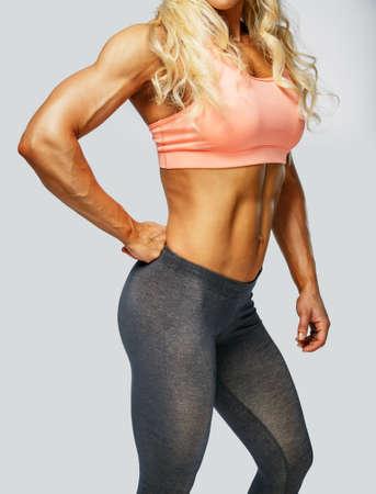 ropa deportiva: Cuerpo de mujer rubia de la aptitud en ropa deportiva sobre fondo gris
