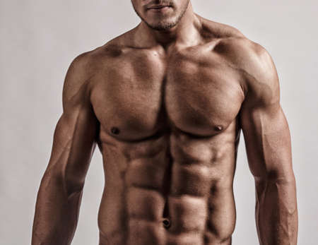 six packs: Portrait in studio of muscular malebody. Isolated on grey background.