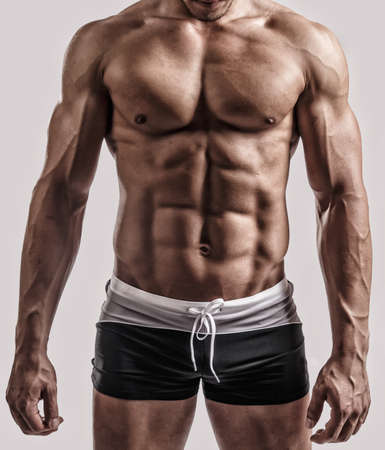 six pack abs: Portrait in studio of muscular male body in black swimming trunks. Isolated on grey background.