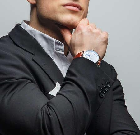 Ritratto di uomo bello in giacca con l'orologio alla mano