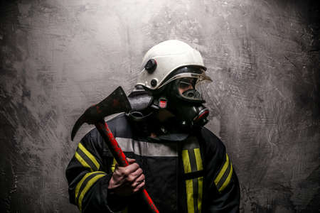 protective helmets: Firefighter in oxygen mask and axe on grey background.