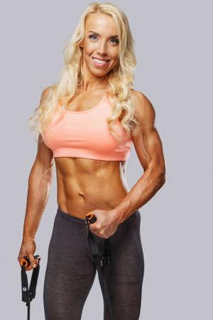 ropa deportiva: Fitness mujer rubia en ropa deportiva sobre fondo gris