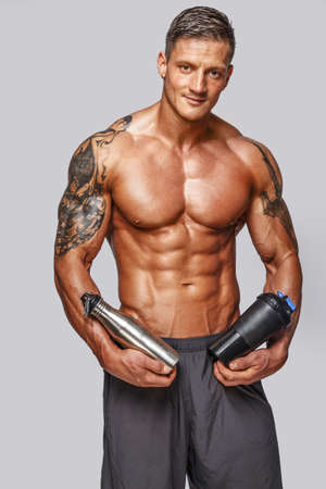 physique: Muscular man with tattos posing in studio Stock Photo
