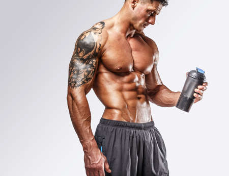 pectorals: Muscular man with tattos posing in studio Stock Photo