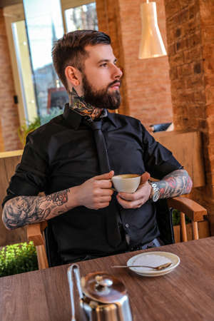 cofe: Guy with beard drinking cofe in restaurant.