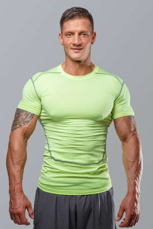 ropa deportiva: Guj muscular en ropa deportiva de color verde. Aislado en gris Foto de archivo