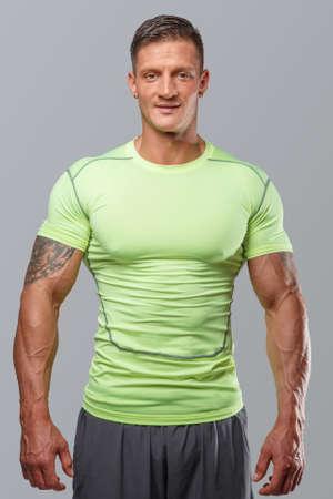 Muscular guj in green sportswear. Isolated on grey