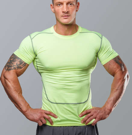 physique: Muscular guj in green sportswear. Isolated on grey