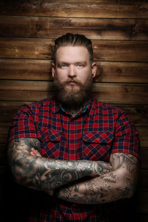 Modern guy with beard and tattos on hands.