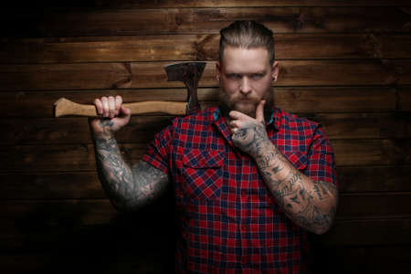 dangerous: Danger man holding axe. Wooden background Stock Photo