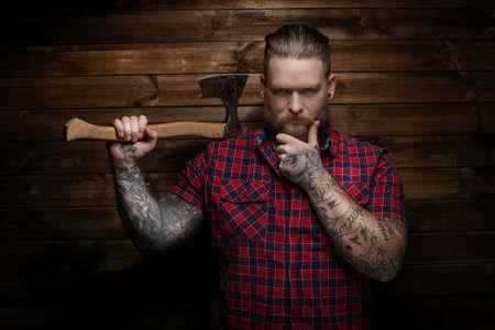 peligro: Hombre del peligro que sostiene el hacha. Fondo de madera