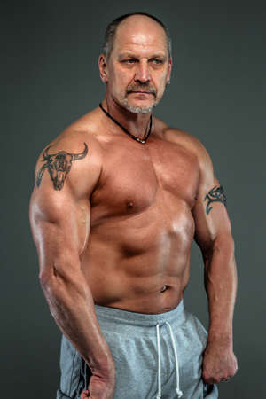 showing muscles: Aged man showing muscles. Studio shoot. Isolated on dark grey