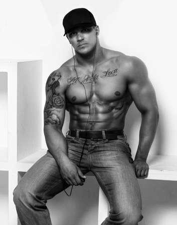 tatouage sexy: gars musclé impressionnant en jeans et une casquette sur fond blanc