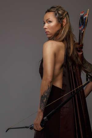 bow arrow: Hermosa mujer elfa arco woth y flechas. Aislado en gris Foto de archivo
