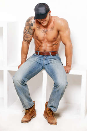 charming: Awesome muscular guy in blue jeans and a cap on white background