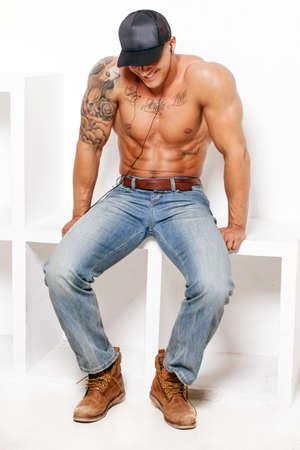 hombres sin camisa: Chico muscular impresionante en blue jeans y una gorra en el fondo blanco