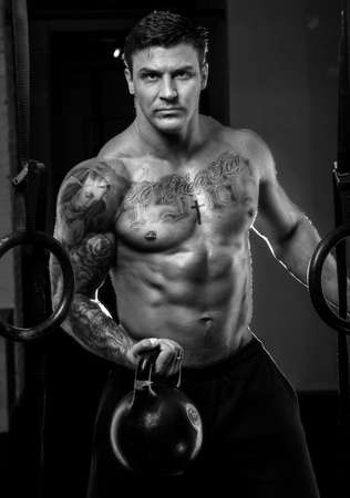 workouts: Muscular man with tattos doing exercises in a gym. Black and white photo