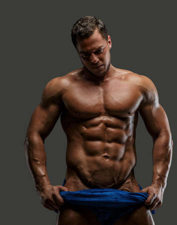 pectorals: Male showing his muscle. Isolated on grey