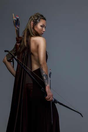 maquillaje de fantasia: Hermosa mujer elfa arco woth y flechas. Aislado en gris Foto de archivo