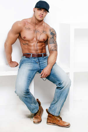 ブルー ジーンズと白い背景のキャップで素晴らしい筋肉男