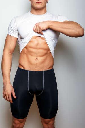 sixpack: Guy in spoertswear showing his muscular stomach