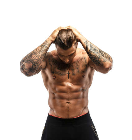 men standing: Brutal muscular tattooed man looking down. Isolated on white Stock Photo