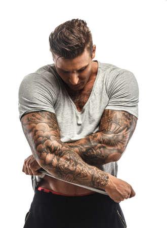 sin camisa: Hombre muscular con tatuajes desvestirse. Aislado en blanco Foto de archivo