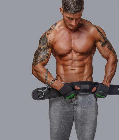 desnudo: hombre en pantalones cortos con el torso musculoso desnudo sosteniendo la cintura poder. Aislado en gris