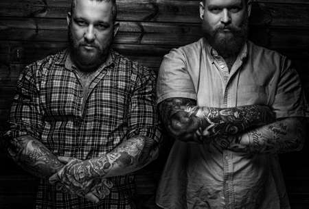 Two brutal huge males with beards in t-shirts posing in front of wooden wall