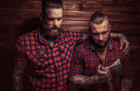 beefcake: Two big brutal males with beards and tattooes and one of them holds axe