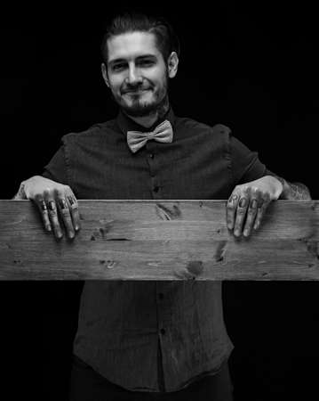 Portrait of a man in blue shirt with grey bow tie and wooden board in his hands. Isolated on black. Stock Photo