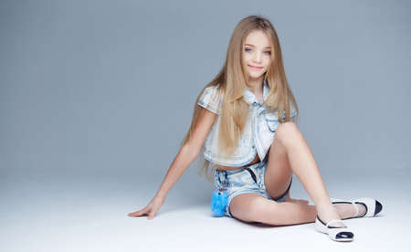 teen legs: Long haired young girl posing in studio on light grey background Stock Photo