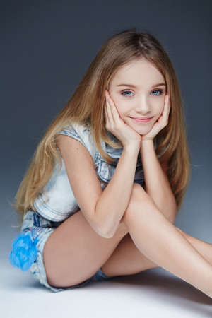 sitting small: Portrait of young cute girl in jeans shorts and tshirt.