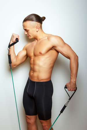 expander: Fitness man doing exercises with expander on grey background
