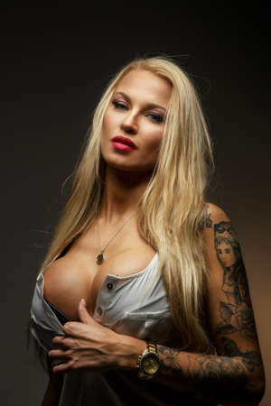 Attractive modern blond female with tattoo on her hand. Isolated on grey Stock Photo